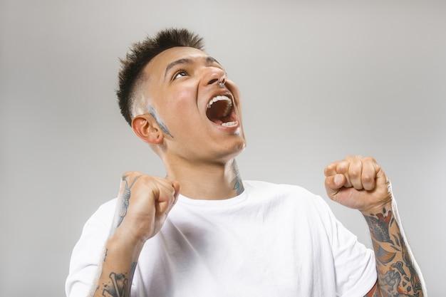 De jonge emotionele boze man die op grijze studioachtergrond schreeuwt