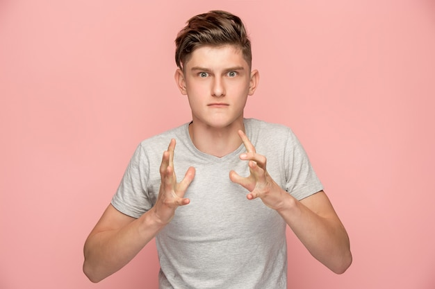 De jonge emotionele boze man die op roze studioachtergrond gilt