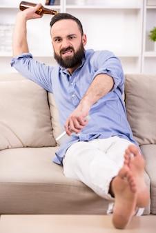 De jonge emotionele man ontspant thuis met bier.