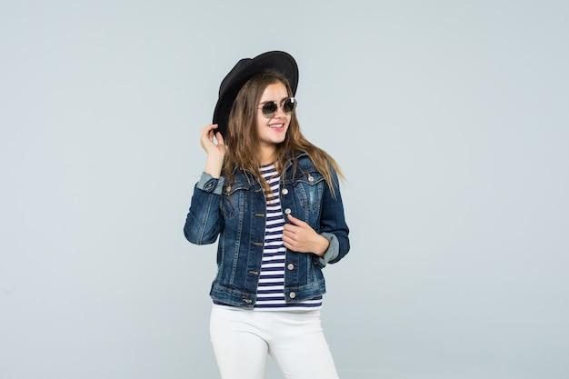 De jonge emotionele vrouw in een zwarte hoed danst op witte achtergrond