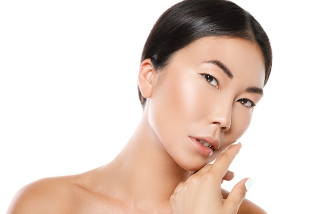 De jonge en mooie aziatische vrouw stelt in studio op witte muur