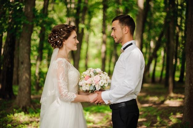 De jonge en mooie bruid en de bruidegom houden elkaar handen