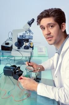 De jonge energieke mannelijke technologie bevestigt elektronisch apparaat