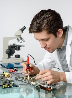 De jonge energieke mannelijke technologie of de ingenieur herstelt elektronika