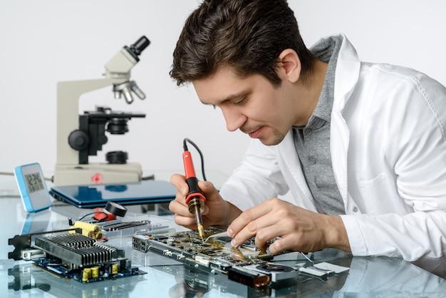 De jonge energieke mannelijke technologie of de ingenieur herstelt elektronische apparatuur