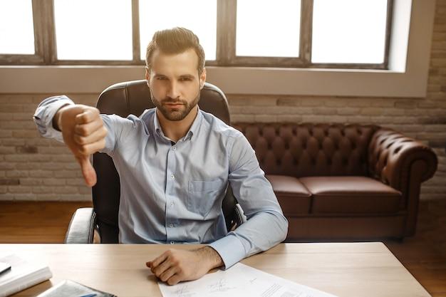 De jonge ernstige knappe zakenman zit aan tafel in zijn eigen kantoor. hij houdt een grote duim ingedrukt en kijkt serieus op camera. helder venster achter.