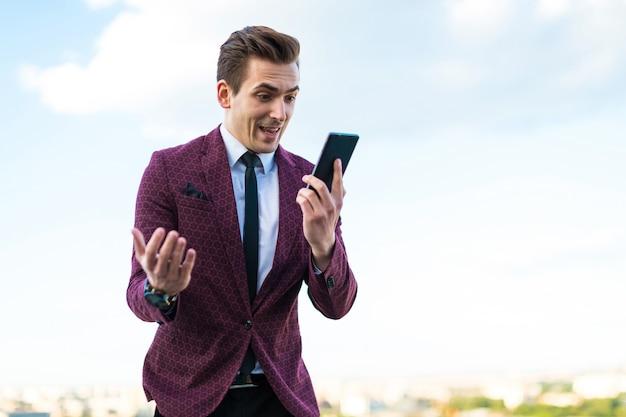 De jonge ernstige zakenman in rood kostuum en overhemd met band bevindt zich het dak en spreekt op de telefoon