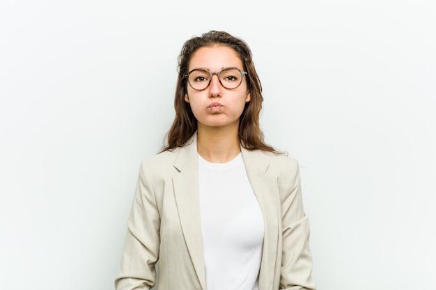 De jonge europese bedrijfsvrouw blaast wangen, heeft uitdrukking vermoeid. gezichtsuitdrukking .