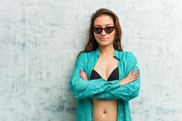 De jonge europese vrouw die bikini draagt die haar gezicht in ongenoegen fronst, houdt wapens gevouwen.