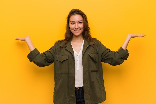 De jonge europese vrouw die over gele achtergrond wordt geïsoleerd maakt schaal met wapens, voelt gelukkig en zeker.
