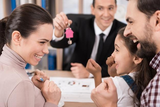 De jonge familie is gelukkig om nieuw huis in bureau van makelaar in te kopen.