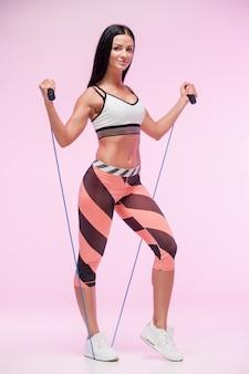 De jonge fitte vrouw traint tegen een roze studioachtergrond met springtouw