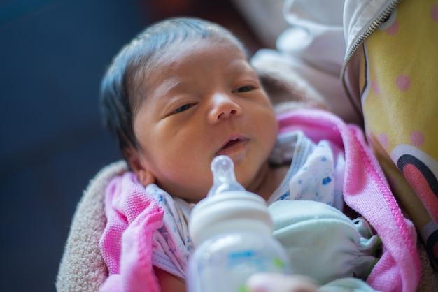 De jonge formule van de moederholding drinkt haar weinig pasgeboren baby