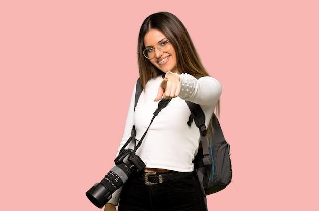 De jonge fotograafvrouw richt vinger op u met een zekere uitdrukking op geïsoleerde roze muur