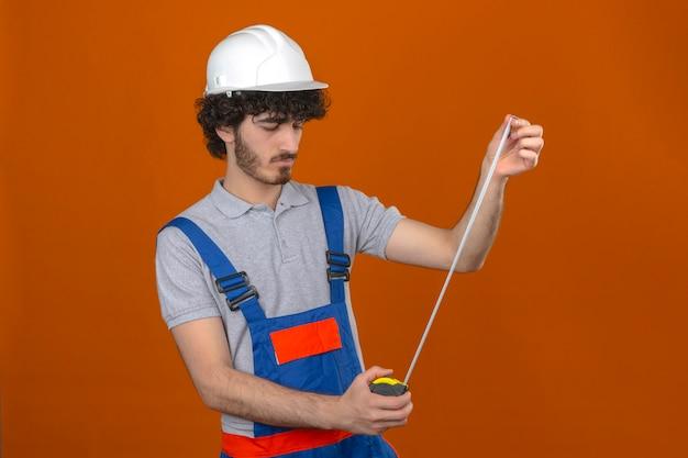De jonge gebaarde knappe bouwer die eenvormige bouw dragen en veiligheidshelm die metend peinzende band in zijn handen bekijken kijkt over geïsoleerde oranje muur