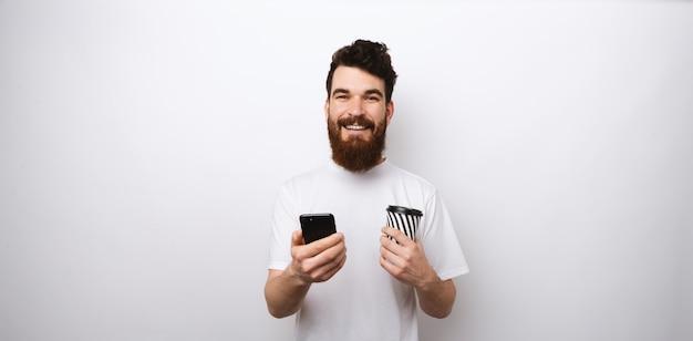 De jonge gebaarde mens in wit overhemd op witte achtergrond die zijn telefoon en een kop van koffie of thee houdt haalt weg of gaat weg.