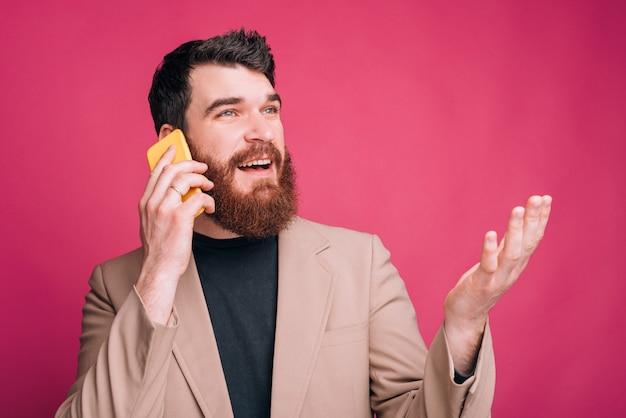 De jonge gebaarde mens legt iets op de telefoon over roze achtergrond uit.