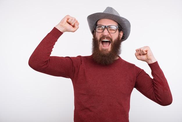 De jonge gebaarde mens met glazen en een grijze hoed schreeuwt met zijn omhoog wapens.
