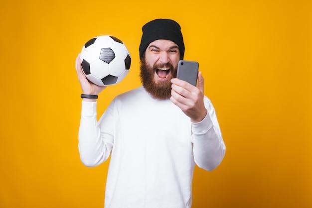 De jonge gebaarde mens neemt een selfie en houdt een voetbalbal dichtbij gele muur.