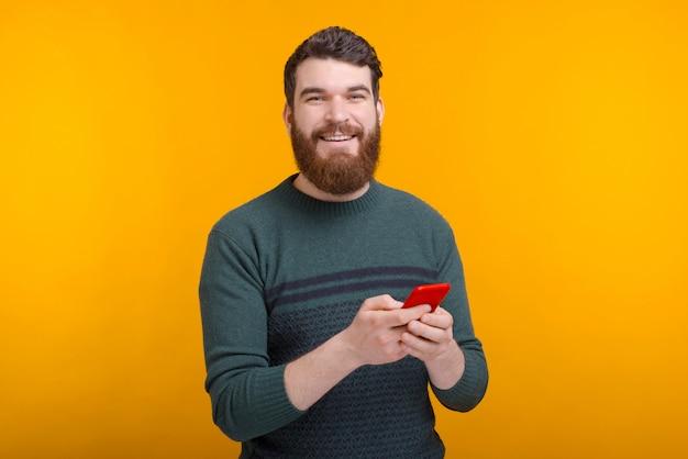 De jonge gebaarde mens typt iets op zijn telefoon of surft op het internet.