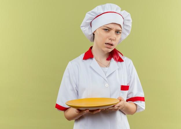 De jonge geërgerde blonde vrouwelijke chef-kok in eenvormige chef-kok houdt plaat en kijkt geïsoleerd op groene muur