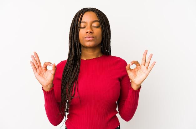 De jonge geïsoleerde afrikaanse amerikaanse vrouw ontspant na harde werkdag, voert zij yoga uit.