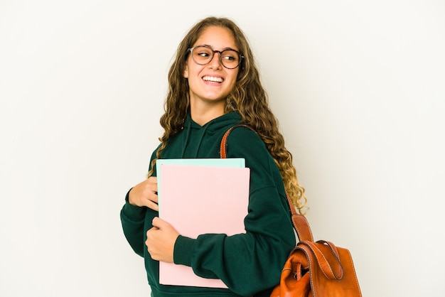De jonge geïsoleerde studentenvrouw kijkt opzij glimlachend, vrolijk en aangenaam