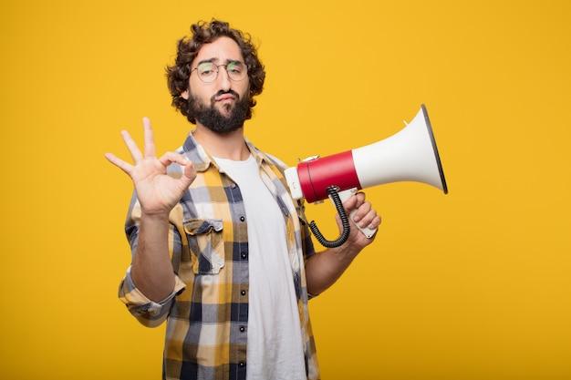 De jonge gekke gekke dwaas stelt met een megafoon. aankondiging co