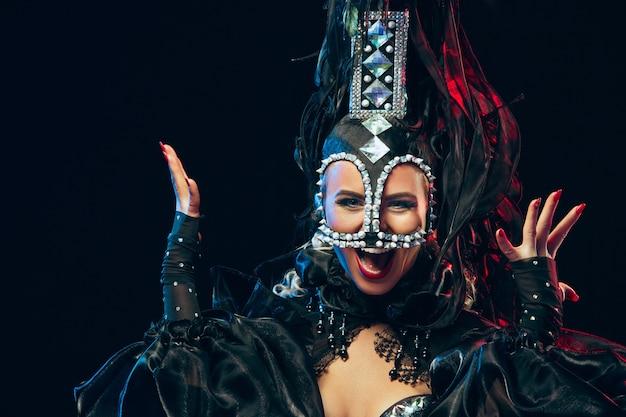 De jonge gelukkig lachende mooie danseres met carnaval jurken poseren op zwarte studio achtergrond