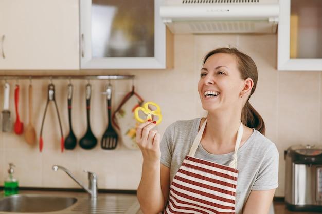 De jonge gelukkige aantrekkelijke vrouw in een schort houdt gele peper in de keuken. dieet concept. gezonde levensstijl. thuis koken. eten koken.