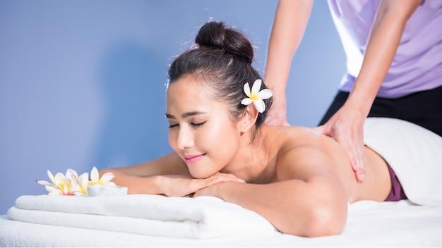 De jonge gelukkige aziatische mooie vrouw ontspant in kuuroord. lichaamsverzorging behandeling.