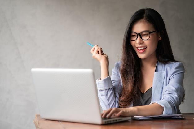 De jonge gelukkige aziatische onderneemster in blauw overhemd die van huis werken en computerlaptop gebruiken en idee voor haar zaken denken
