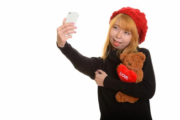 De jonge gelukkige aziatische vrouw glimlacht en houdt teddybeer met hoort