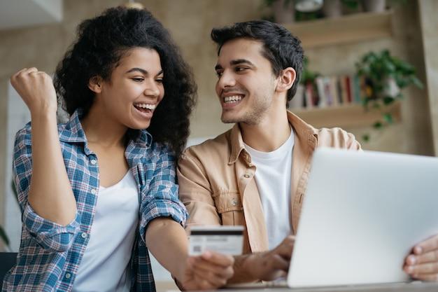 De jonge gelukkige creditcard van de paarholding, online winkelend, thuis zittend