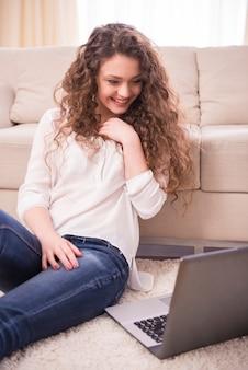 De jonge gelukkige glimlachende vrouw met laptop werkt thuis.
