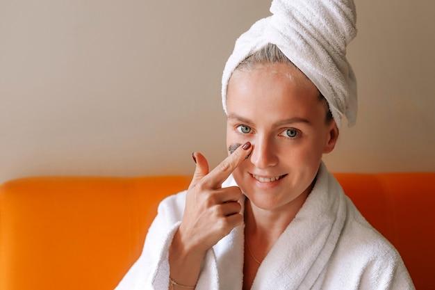 De jonge gelukkige kaukasische vrouw in handdoek zet een masker op haar gezicht.