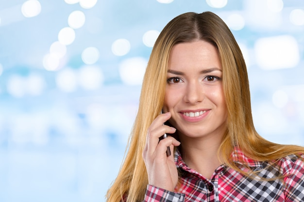 De jonge gelukkige kaukasische vrouw roept met een mobiele telefoon