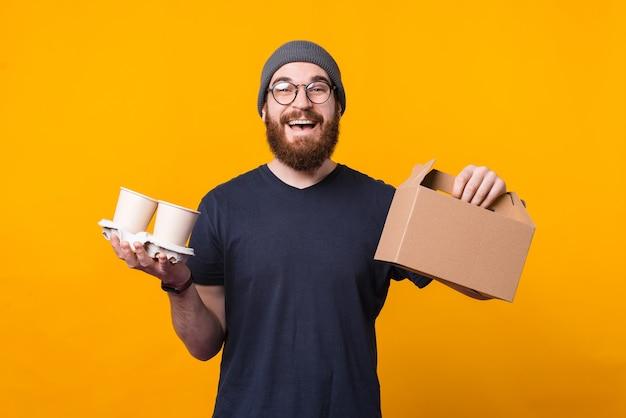 De jonge gelukkige mens houdt een leveringsdoos en een kop warme drank vast die er vrolijk uitziet