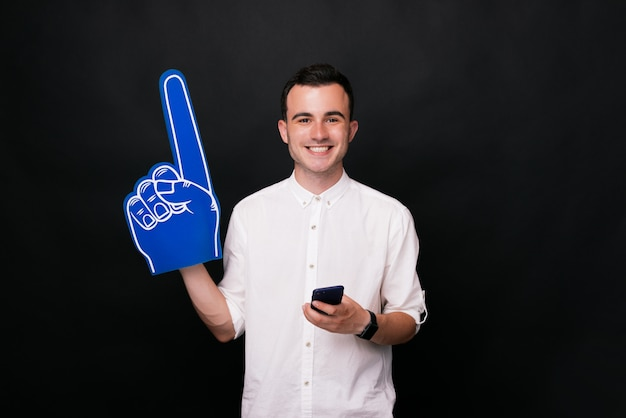 De jonge gelukkige mens in wit overhemd houdt blauwe schuimhandschoen en een telefoon op een zwarte achtergrond.