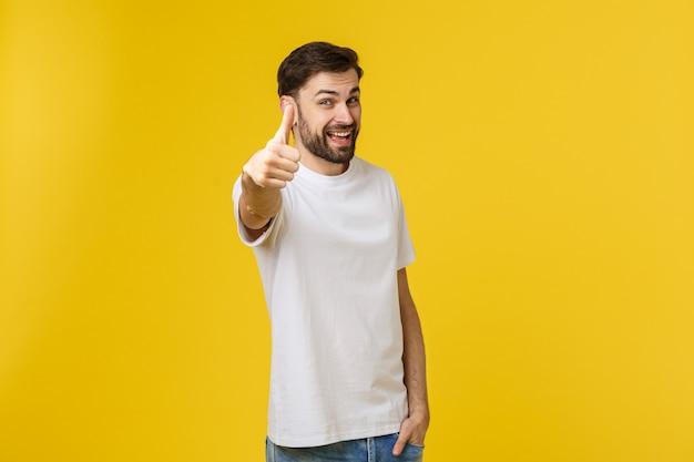De jonge gelukkige mens met duimen ondertekent omhoog in toevallig geïsoleerd op geel