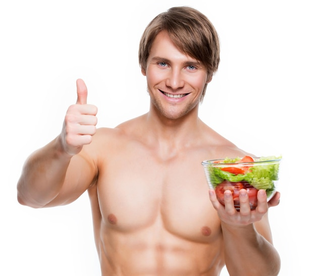 De jonge gelukkige spiermens die een salade houdt en duimen toont ondertekent omhoog over witte muur.