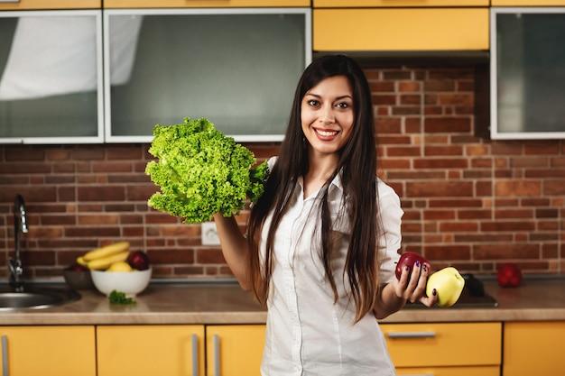 De jonge gelukkige vrouw houdt twee appelen en sla in haar handen. een vrouw die en zich in de keuken thuis glimlacht bevindt. het concept van voeding en gezond eten, het lichaam reinigen