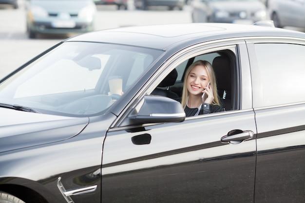 De jonge gelukkige vrouw kocht nieuwe moderne auto