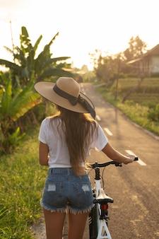 De jonge gelukkige vrouw loopt met een fiets door smalle landweg