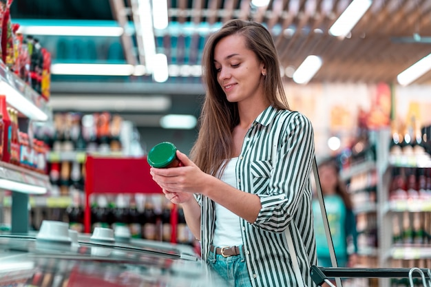 De jonge gelukkige vrouw met boodschappenwagentje kiest, controlerend productenetiket en het kopen van voedsel bij de kruidenierswinkel