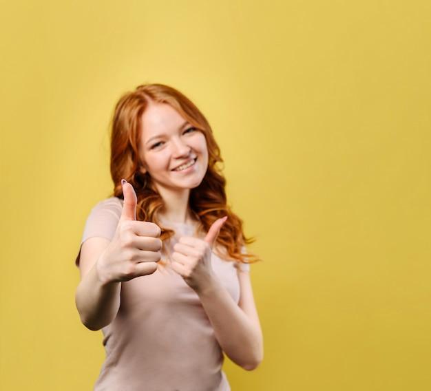 De jonge gelukkige vrouw met rood haar toont duim in goedkeuring