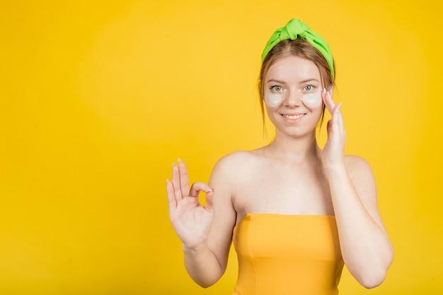 De jonge gelukkige vrouw met vlek onder ogen die op gele muur wordt geïsoleerdt toont oke zucht. goede huidverzorgingsroutine