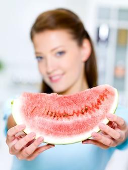De jonge gelukkige vrouw toont een rode watermeloen