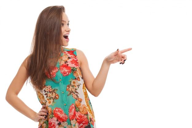 De jonge gelukkige vrouw toont op iets