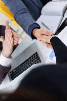 De jonge gelukkige zakenlieden hebben vergadering in bureau schudden elkaar de hand